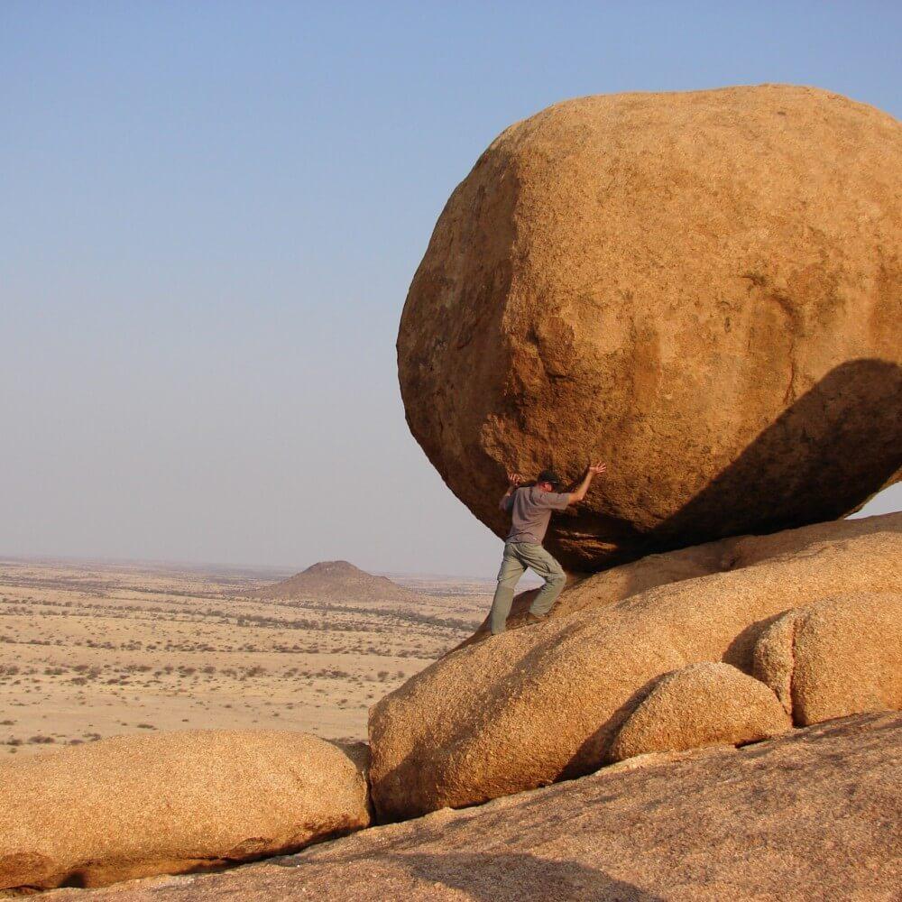 Mann schiebt großen Felsen