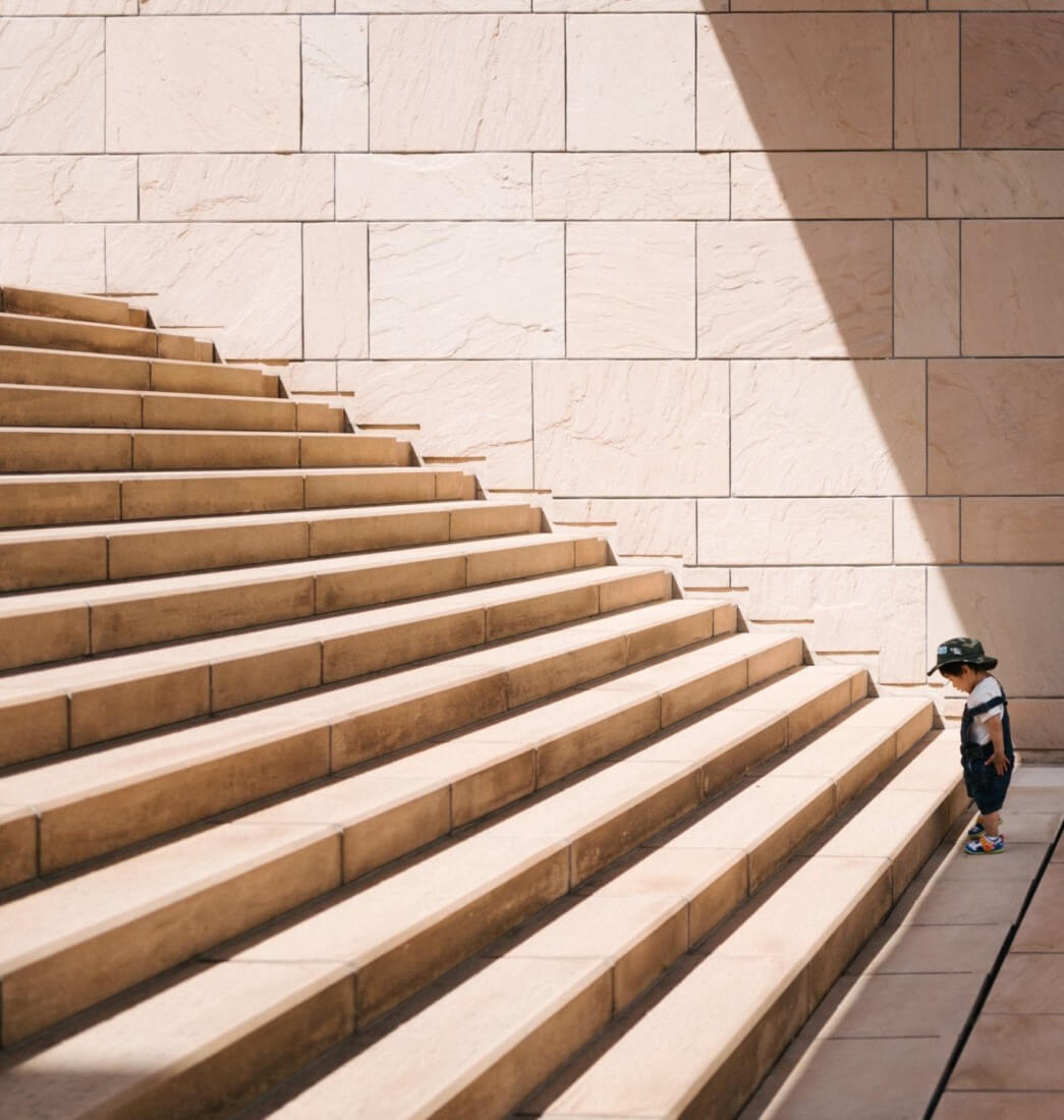 Kleiner Junge vor hellbrauner Treppe