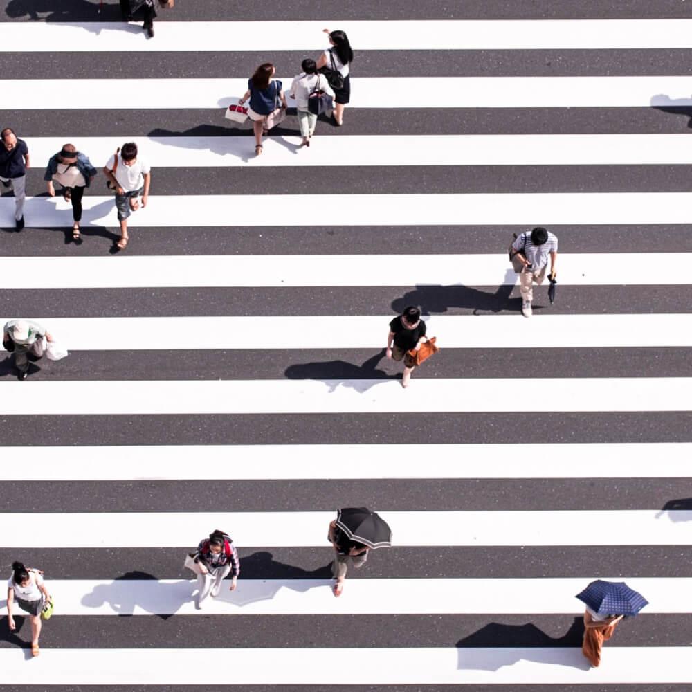Menschen überqueren einen großen Zebrastreifen