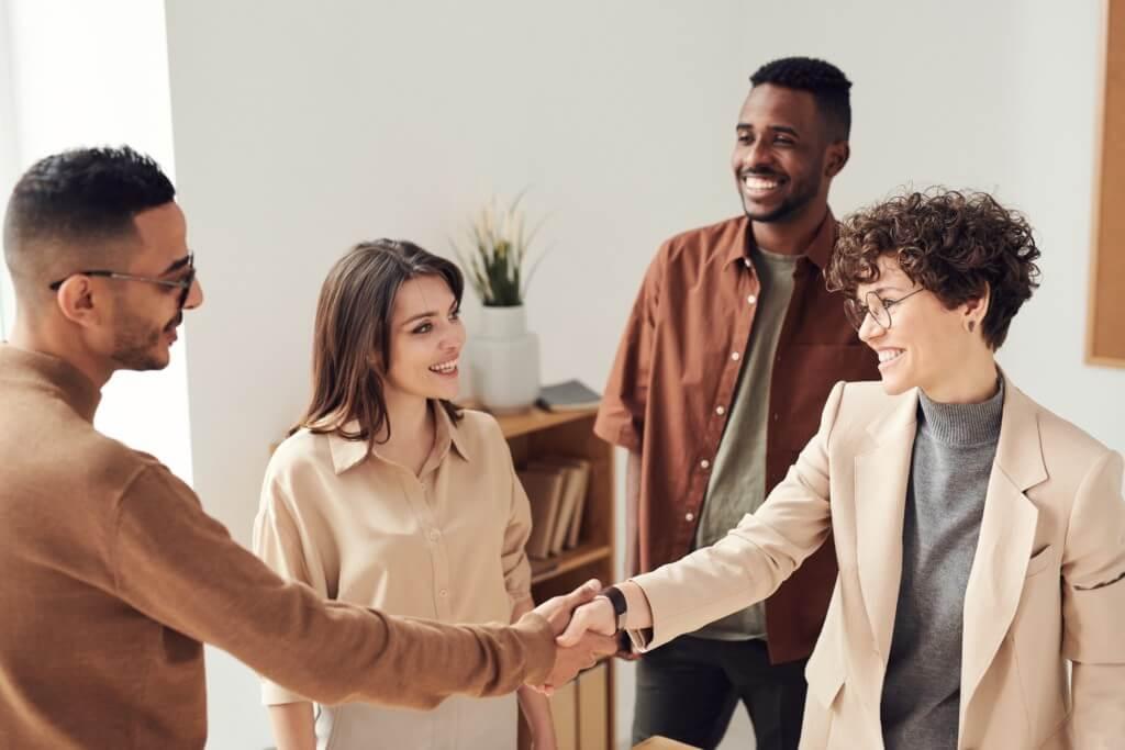 Marketing Meeting in dem zwei Menschen sich die Hände geben