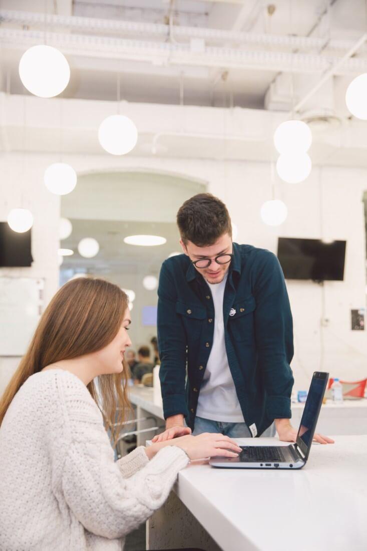 Marketingmanager und Managerin arbeiten an einem Laptop