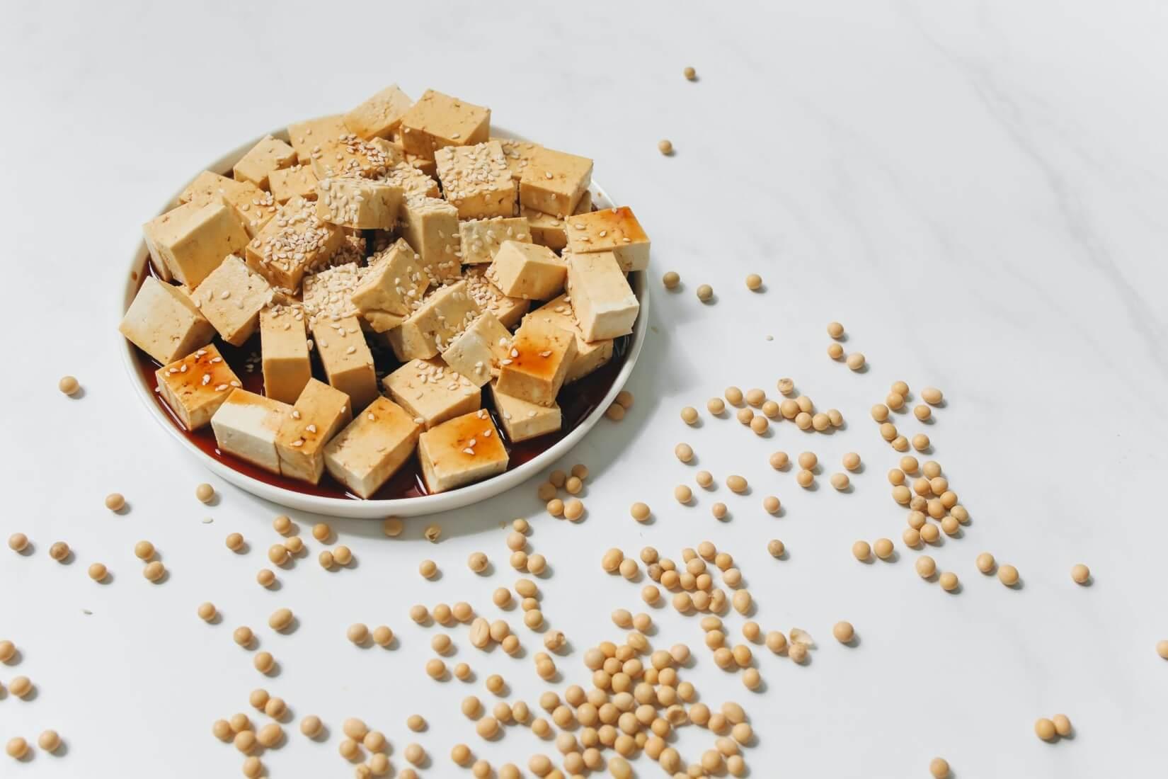 Schüssel mit Tofu und Sojabohnen daneben