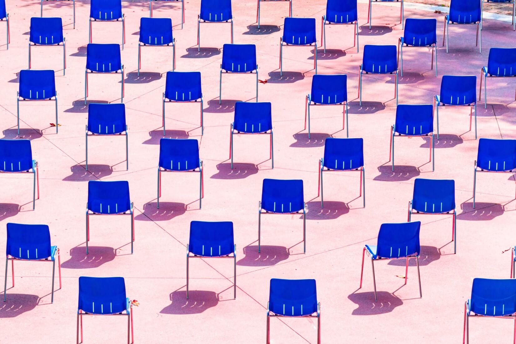 Viele blaue Stühle auf rosa Hintergrund